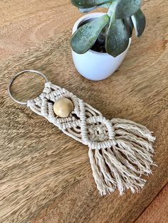 Handmade oversized macramé keychain. Made using 3mm cotton cord and wooden bead. Hung on large steel ring. These are a super cool accessory for your keys and they make awesome gifts! Measures 2W X 6L Steel ring is 2 in diameter This item is finished and ready to ship. Custom orders