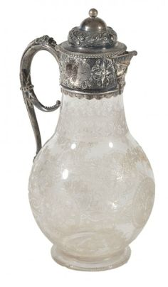 A Victorian silver mounted glass claret jug with a band of foliage to the domed lid ad mount, with a mask spout and a C-scroll handle, the glass body engraved and etched with flowers and an entwined band