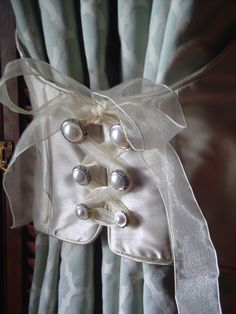 satin, pearl button and wired ribbon makes a sweet curtain tieback.  or to tie a large bunch of roses together--wedding bouquet maybe