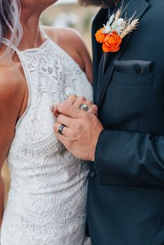 Bride and groom holding hands with wedding rings and lace high neck dress and black suit with orange boutineer in this fall styled wedding shoot in Logan Utah by Kristi Alyse Photography. northern utah boho wedding lace white high neck dress orange flowers logan utah meaningful photography wedding and family photographer quality photography #northernutahweddingphotographer #loganutahweddingphotographer #meaningfulphotography #bohowedding #bohoweddingdress #utahweddings #weddingrings…