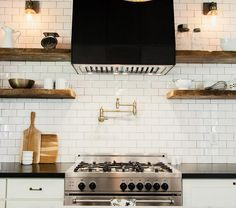 Country kitchen boasts white cabinets paired with black countertops and a white subway tiled backsplash with black grout. A black kitchen hood, flanked by stacked wood floating shelves, stands over a gold swing arm pot filler and a stainless steel stove. Kitchen Hoods, Kitchen Stove, Kitchen Shelves, Kitchen Tiles, Kitchen Flooring, Wood Shelves, Kitchen Countertops, New Kitchen, Kitchen Design