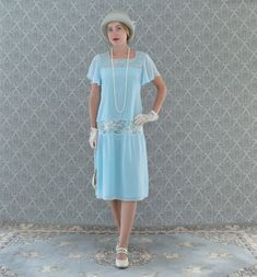 A sweet feminine drop waist dress inspired by 1920s fashion. The dress is made of chiffon and lace fabrics. The chiffon is light blue and the lace is silver grey, which shimmers slightly. The design is streamlined, loose fitting, with drop waist and almost straight bodice. The dress is fully lined with light blue fabric. It comes with short ruffled sleeves . A small rolled hem is used for the ruffled sleeves to allow them to flow and drape freely. Very pretty and professionally made. The…