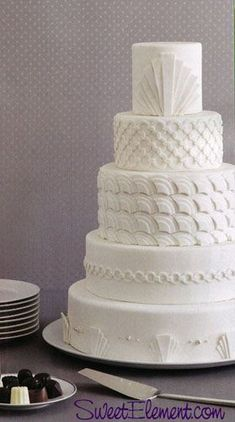 Gorgeous all-white art deco themed wedding cake with a different design in each…
