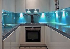 This River Thames apartment in Wapping, London has a compact galley kitchen which needed a piece from us. The client knew she wanted a Tree of Life design but the space between the worktops and the cupboards was limited. Lisa created a soft pastel blue grey to compliment the pale kitchen. The tree has a twisted trunk and then the branches spread and fall towards the sides.
