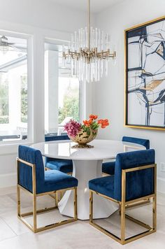 A round white dining table finished with gold and blue sapphire dining chairs under a brass and lucite chandelier.Get inspired by these dining room decor ideas! From dining room furniture ideas, dining room lighting inspirations and the best dining r Dining Room Paint, Dining Room Design, Dining Room Furniture, Modern Furniture, Furniture Design, Furniture Ideas, Fine Furniture, Gold Furniture, Business Furniture