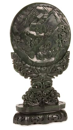 CHINESE CARVED JADE TABLE SCREEN AND STAND, QING DYNASTY/EARLY REPUBLIC PERIOD. Depicting Taoist figures in a mountainous setting with incised inscription on verso carved in Manasi nephrite contained in a matching pierce carved cradle with scrolling foliates.