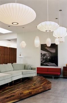 A squadron of George Nelson bubble lamps appears to be flying in formation across a modern-day Modernica showroom. George Nelson, Bauhaus, Pendant Lamp, Pendant Lighting, Pearl Pendant, Deco Luminaire, Nelson Bubble Lamp, Mid Century Modern Lighting, My Living Room