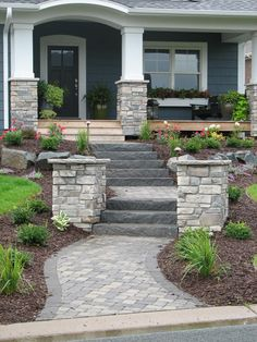 Paver walkway, natural stone steps and flanking pillars create a dramatic entrance