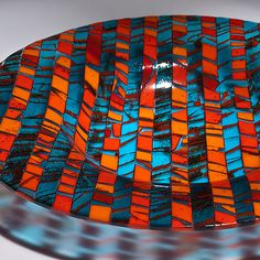 Fused and slumped glass bowl in orange and turquoise. Sheets of art glass are created and fired, then cut and assembled to create this vivid bowl.