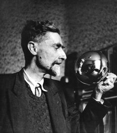 """M.C. ESCHER holding a round style mirror used for his famous """"Self-Portrait In Spherical Mirror"""" 1935"""
