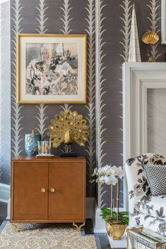 Close up of a wood cabinet in a Hamptons bedroom with vine wallpaper and a gold peacock