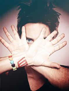 Jared Leto - palms exposed, one eye shown to the world, red ink on wrist (tattoo) RAINBOW heart bracelet (gift from fan? his own collection of positive energy jewelry?)