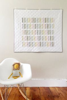 Inspired by Scandinavian interiors, this modern baby quilt features solid pastel stripes arranged in color order and set against a white background. The backing