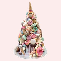"Croquembouche unicorn cake -- ""It looked more magical as we kept building it up with sprinkle glazed profiteroles and eclairs, colourful macarons, pretty pastel baked doughnuts, piped buttercream flowers, chocolate pearls, Ferrero rocher cones, ""soft serve"" buttercream cones and candied popcorn. And WOW.  Just look at it!"""
