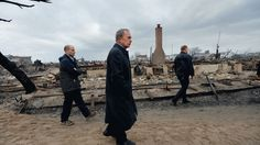 New York City Mayor Michael Bloomberg (center) views damage in the Breezy Point area of Queens in New York on October 30, 2012 after fire destroyed about 80 homes as a result of Superstorm Sandy.