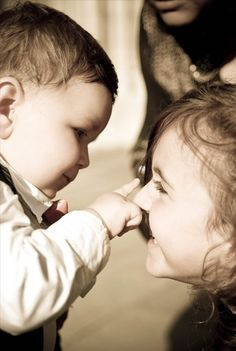 A baby boy pinches his sister's nose.. cute..