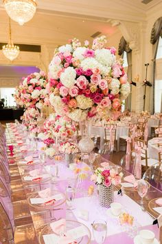 Amazing tablescape with pink and white floral centerpieces sitting on the clear table - GORGEOUS! Photo by Chris Humphrey Photographer. #wedding #centerpiece #decor #pink