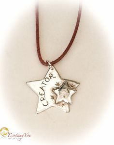 """Handcrafted fine silver pendant with a 'Creator' medallion on a light brown leather cord (length 42cm) . No 232. The word """"CREATOR"""" is handcarved. The big star measures 26 mm in diameter and has 1 little star coming with it measuring 12 mm in diameter. The embedded white cubic zirconia stone measures 4 mm in diameter. The front is high polished and the back has a matt finish.   It reminds you of what you are: a CREATOR!"""
