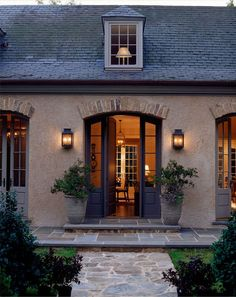 Lanterns, arched glass doors, exterior color and slate roof, stone planters, welcoming entrance, greys, black door: