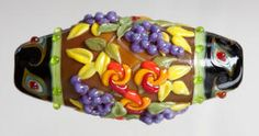 """MEXICAN POTTERY by Kim Fields     ~        All the colors of a fiesta grace this happy piece. Made of polished glass with . 1.75"""" long x .85"""" diameter"""
