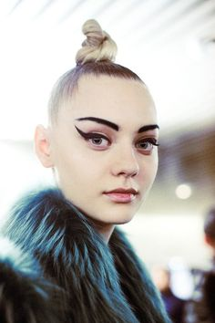 Graphic eyeliner, top knot and blue fur backstage at Jean Paul Gaultier AW14 PFW. More images here: http://www.dazeddigital.com/fashion/article/19080/1/jean-paul-gaultier-aw14