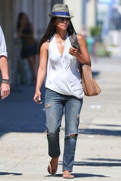 Halle Berry in ripped jeans, a halter top and flip-flops. She completed the look with a stylish gray-and-blue fedora and a nude snakeskin purse.