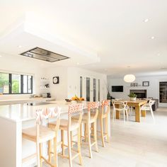 White open plan kitchen in shades of white with contrasting bar stools