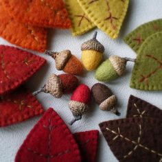 A batch of wool acorns surrounded by coordinating wool leaf ornaments. These colors make me happy.