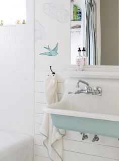 Turquoise blue bathroom features upper walls clad in Hygge & West Daydream French BLue Wallpaper and lower walls clad in shiplap lined with a turquoise blue trough sink, Kohler Brockway Sink, fitted with two faucets and a full length mirror.