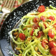 Pesto zoodles, this low carb, gluten free vegetarian recipe features yellow and green zucchini pasta, basil parmesan pesto, creamy mozzarella, fresh tomatoes and pine nuts.