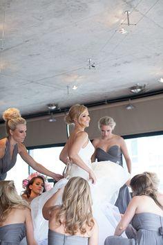 Bridesmaids in gray dresses help the bride get ready. Cute! photos by Miller + Miller Photography   junebugweddings.com