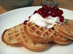 """Norwegian Sour Cream Waffles, called """"Vafflor,"""" topped with whipped cream and lingonberries."""