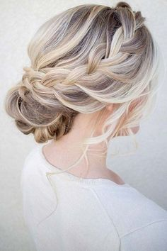 Plait your hair and then twist it into an elegant updo for a gorgeous modern wedding hairstyle.