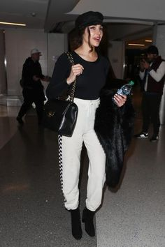 Olivia Culpo wearing Chanel Quilted Flap Xl Bag, Lack of Color Riviera Cap, Unreal Fur Delicious Jacket in Black, Stella McCartney Checker Side Pants, Aquatalia Erika Boots and Wolford Image String Body