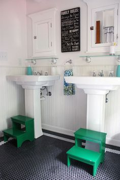 Two stand alone sinks in the kids bathroom with step stools in green.