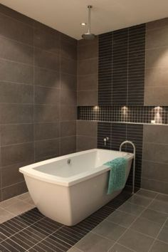 Rain shower over a deep, freestanding bath.  Gorgeous integrated floor to ceiling tiling adding style and luxury to any bathroom.