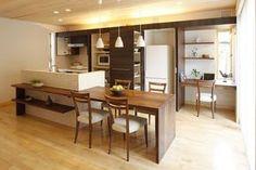 ブラックウォールナットのテーブルと一体の横型対面キッチン。壁面収納には冷蔵庫、電子レンジなど、手の届く範囲に必要なものが収納できます。 キッチン アイランド インテリア カウンター タイル ダイニング おしゃれ 壁面収納 ウッド 