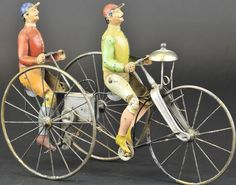 France, rare early hand painted tin bicycle toy, depicts two riders on three-wheeled cycle, clockwork allows bicyclists' legs to seemingly propel the cycle in a natural movement.