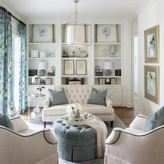 Just off the kitchen, the keeping room is a great place to relax, chat with the cook or enjoy views of the pool. Creamy whites and soft blues mix for a welcoming, airy space, which pairs a tufted sofa and ottoman with armchairs featuring nailhead trim. Built-in bookshelves are artfully decorated to highlight the homeowners' collection of pretty accessories and art.