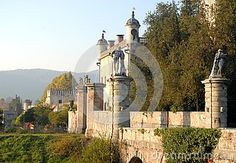 Photo made at the castle Catajo in the province of Padua in Veneto (Italy). In the picture, made at first autumn afternoon, we see a detail of the bridge, with the two large statues, which connects the road to the courtyard of the massive central body of which one sees a part. It also sees the whole south-facing walls illuminated by the sun and immersed in thick vegetation.