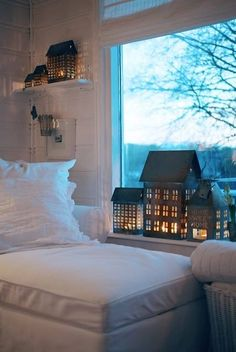 lighted houses on window sill and shelf. I like the trees in the back ground