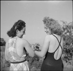STAY AT HOME HOLIDAYS: ENTERTAINMENT AND RELAXATION IN WARTIME LONDON, ENGLAND, 1943. Pinkie Barnes and Peggy Franks play with their cat in the garden. They are both wearing swimsuits as they are enjoying a spot of sunbathing as part of their 'holiday at home'.