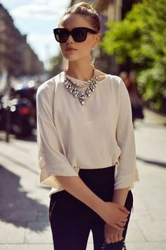 Beige lose blouse, black pants and a jeweled necklace. Nice!