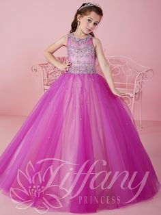 Your little girl will feel like a princess wearing this gorgeous Tiffany Princess pageant dress. This Tiffany Princess pageant dress 13460 has an illusion jewel neckline, rhinestone and chain beaded bodice, and a tulle ball gown skirt. The lace up back gives a huge advantage for the perfect fit. Features: Lace Up Back Silhouette: Ball Gown  Neckline: Illusion Neckline  Fabric: Tulle Sizes Available: 0 through 16   Colors Available: Magenta/Champagne, Marine Blue/Champagne and All White