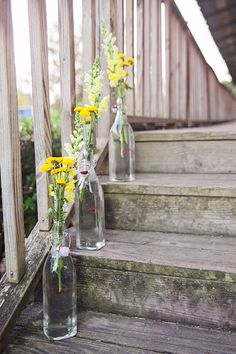 These are the same bottles I have in my cabinet!!  wildflowers in glass bottles brighten up a staircase