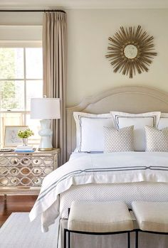Gray bedroom features a gold sunburst mirror placed over a gray velvet headboard on bed dressed in white and gray hotel bedding as well as a linen bench placed at the end of the bed.