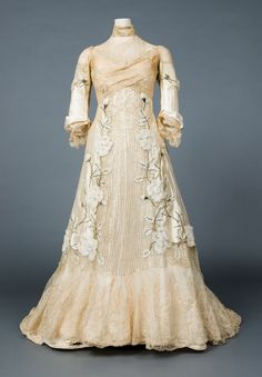 Evening gown, 1900.    The trained evening gown is of ivory silk taffeta and chiffon with ecru lace insertions, applied chiffon flowers embroidered with silver thread and hundreds of vertical pin tucks. But the most striking element is the thousands of dazzling silver sequins that cover the gown in vertical rows.