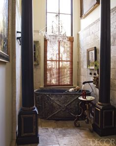 Eclectic bathroom, designed by Gwynn Griffith. A zinc bathtub and a tumbled-travertine floor in the guest bath; a marble platter atop an Italian base serves as a table.