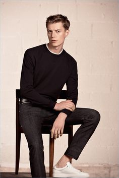 Janis Ancens sports a crewneck sweater with slim-fit jeans and white sneakers by BOSS Hugo Boss.