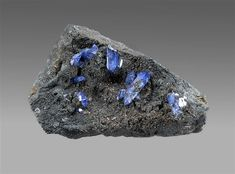 """Scorodite on Beudantite - Tsumeb, Namibia, 8 x 5 x 3 cm. This riveting display-sized matrix scorodite is a """"jewel"""" with astonishing brilliant blue color, in crystals to almost 2 cm in length. The crystals are perched on a sparkling matrix of brilliant brown-black beudantite, making this also an uncommonly rich beudantite specimen. Purchased from dealer Herb Obodda, who had gotten it from a private collection just before Tucson of 2001. Photo John Schneider"""